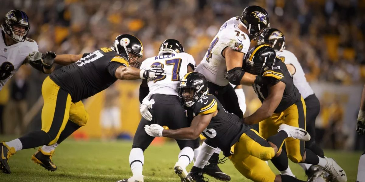 Steelers linebacker Vince Williams is assisted by Cam Heyward in tackling a Baltimore Ravens rusher